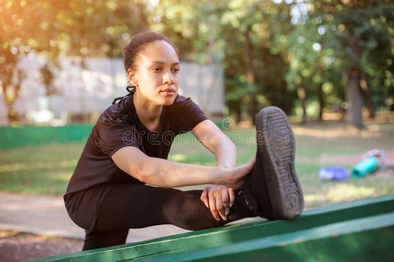 utomhus utbilda Färdig ung kvinna som sträcker henne ben royaltyfri bild