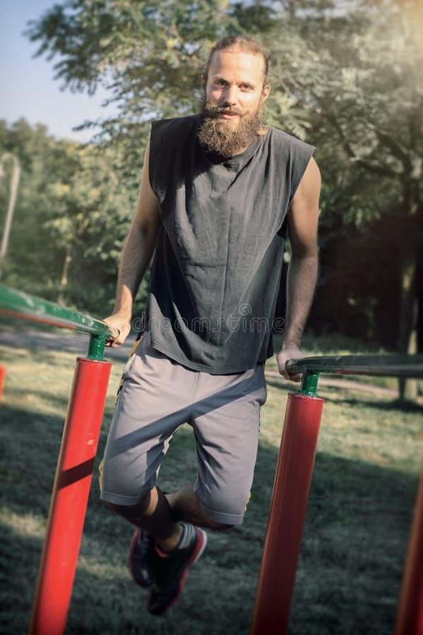 utomhus utbilda Man som gör biceps- och tricepsdopputbildning royaltyfri foto