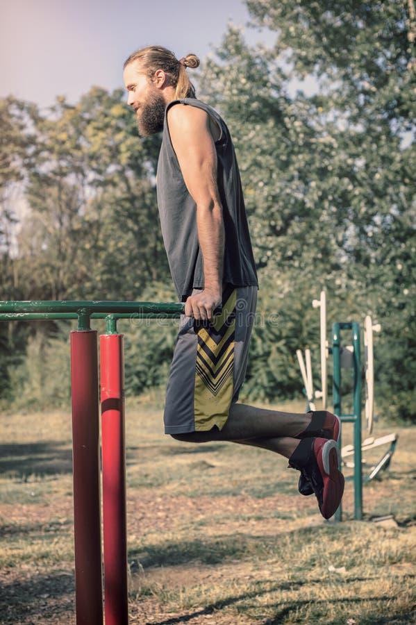 utomhus utbilda Man som gör biceps- och tricepsdopputbildning royaltyfri bild