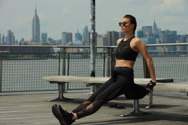Utomhus- utbildning av den unga attraktiva brunettkvinnan royaltyfri foto