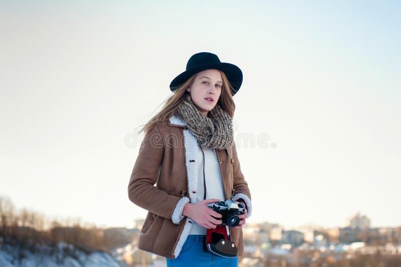 Utomhus- vinterlivsstilstående av den nätta blonda kvinnan med den retro kameran arkivfoton