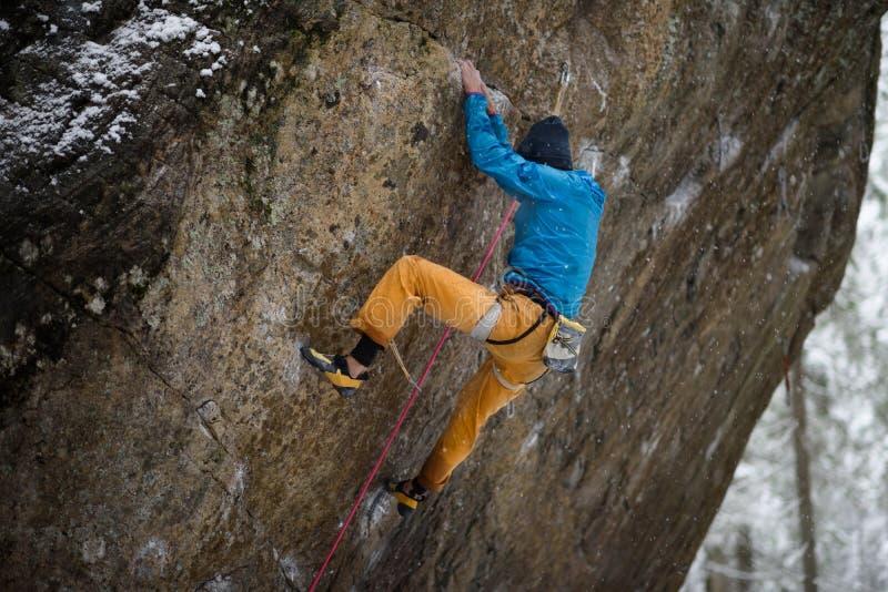 Utomhus- vintersport Vagga klättraren som stiger en utmanande klippa Extrem sportklättring fotografering för bildbyråer