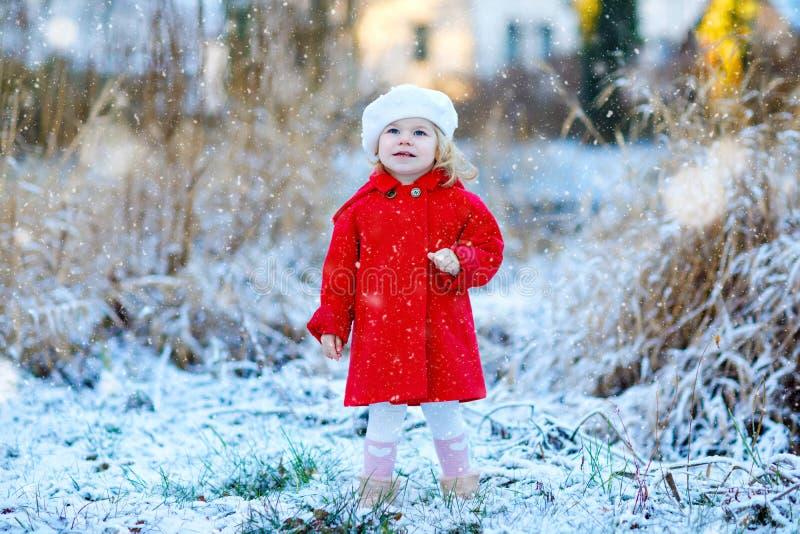 Utomhus- vinterstående av den lilla gulliga litet barnflickan i rött lag och den vita modehattbarreten Sunt lyckligt behandla som arkivfoton