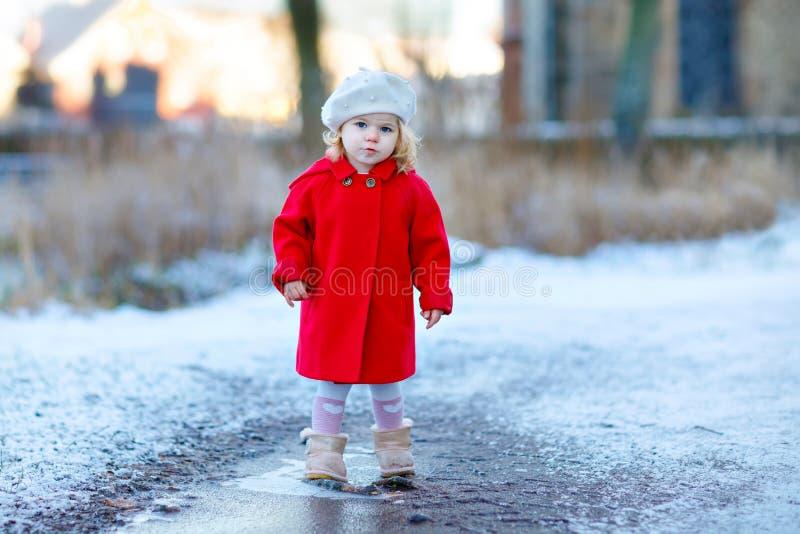 Utomhus- vinterstående av den lilla gulliga litet barnflickan i rött lag och den vita modehattbarreten Sunt lyckligt behandla som royaltyfri foto