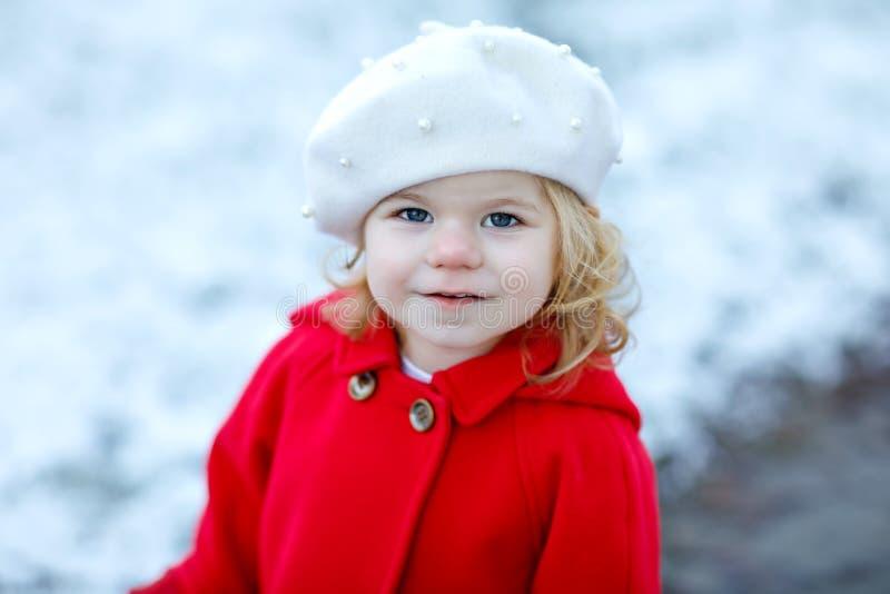 Utomhus- vinterstående av den lilla gulliga litet barnflickan i rött lag och den vita modehattbarreten Sunt lyckligt behandla som royaltyfri bild