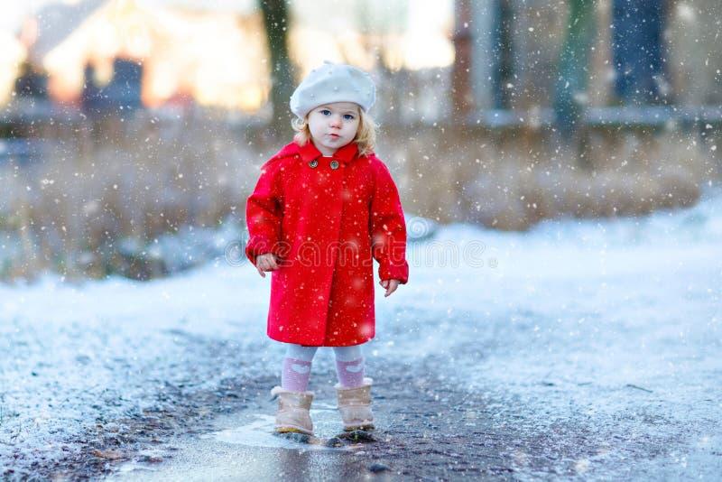 Utomhus- vinterstående av den lilla gulliga litet barnflickan i rött lag och den vita modehattbarreten Sunt lyckligt behandla som arkivbild
