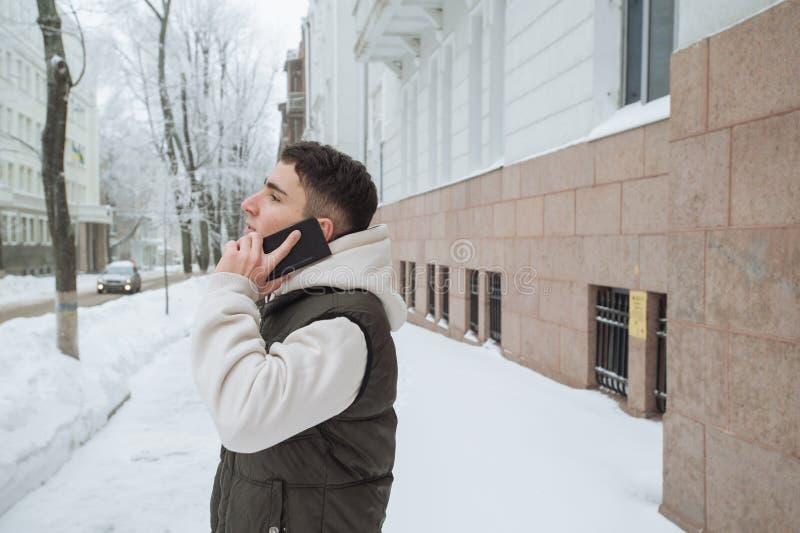 Utomhus- vinterstående för ung stilig man med telefonen Härlig tonåring i hans omslag och väst som poserar på en stadsgata, royaltyfri fotografi
