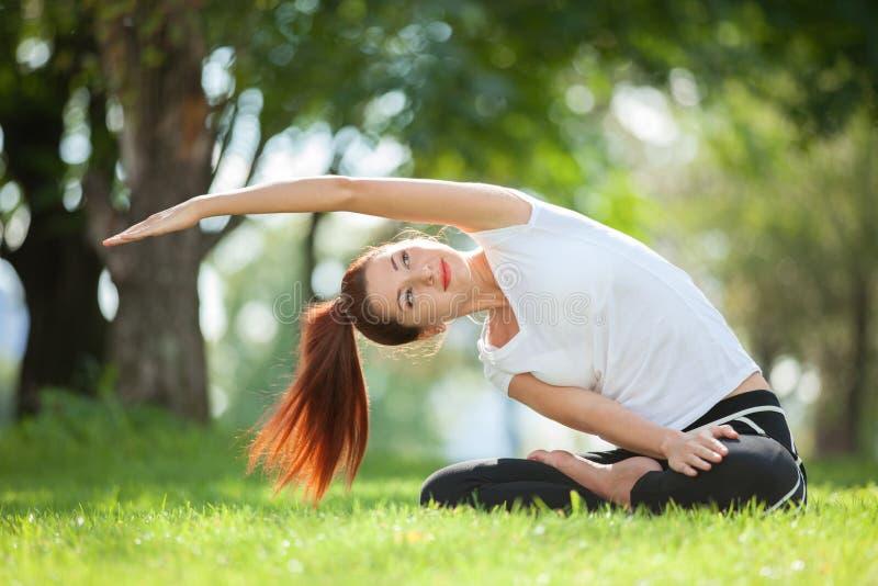 utomhus- yoga Den lyckliga kvinnan som gör yogaövningar, mediterar i parkera Yogameditation i natur sund livsstil för begrepp arkivbild