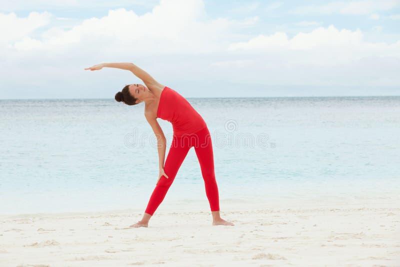 utomhus- yoga Den lyckliga kvinnan som gör yogaövningar, mediterar på stranden Yogameditation i natur Begrepp av den sunda livsst royaltyfria bilder