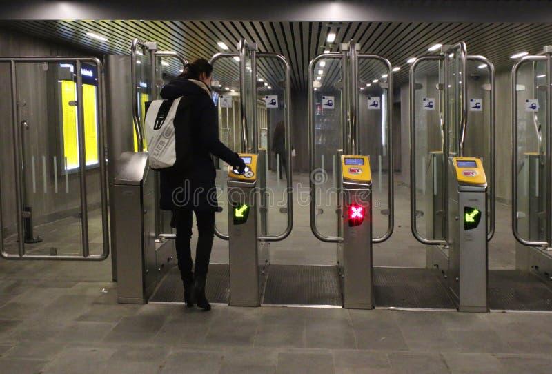 Utrecht, Нидерланд, 15-ое февраля 2019: Женщина выходя центральный вокзал Utrecht до конца оформляет заказ ворота NS стоковое фото rf