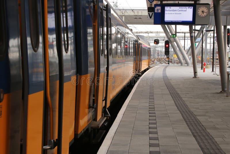 Utrecht holandie, Marzec 8, 2019: Intercity, żółty pociąg z drzwiami, otwiera gotowego wchodzić do fotografia stock