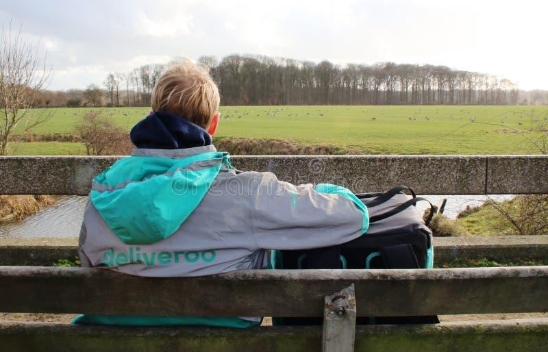 Utrecht, los Países Bajos, el 19 de febrero de 2019: Persona de Deliveroo, esperando solamente el orden siguiente con una hermosa fotos de archivo libres de regalías