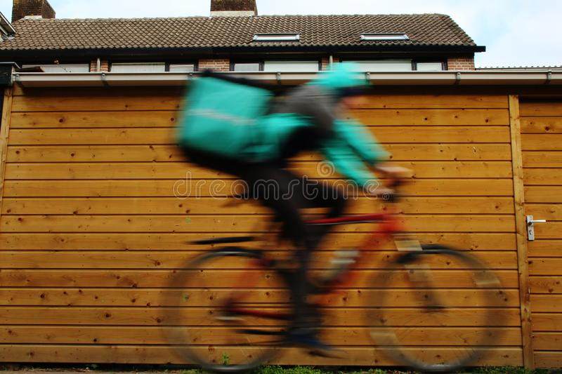 Utrecht, the Netherlands, February 19, 2019: A deliveroo freelancer on his bike, blurry because of dangerous high speed royalty free stock images