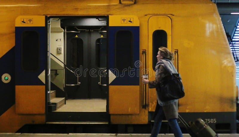 Utrecht, os Países Baixos, o 15 de fevereiro de 2019: Uma mulher que trava o trem interurbano do NS com uma xícara de café fotos de stock royalty free