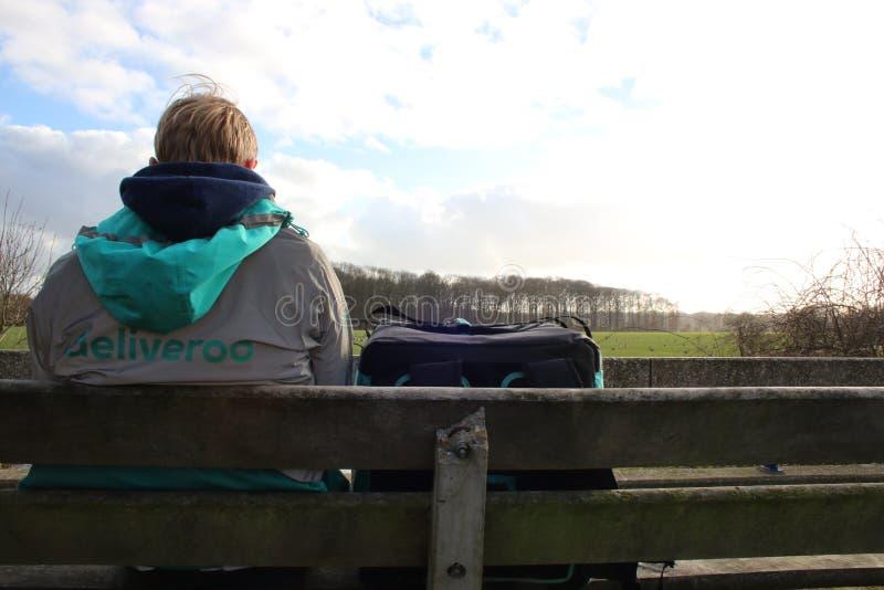 Utrecht, Paesi Bassi, il 19 febbraio 2019: Persona di Deliveroo, aspettante da solo l'ordine seguente con una bella vista fotografia stock