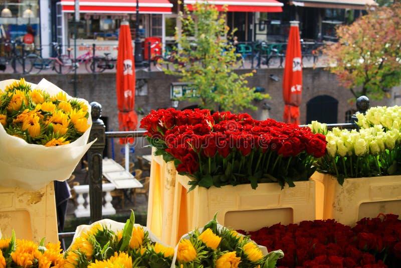 UTRECHT SOM ÄR NEDERLÄNDSK - OKTOBER 20 2018: Sikt på buketter av gula solrosor och röda tulpan nära vattenkanalen på blommamarkn royaltyfri bild