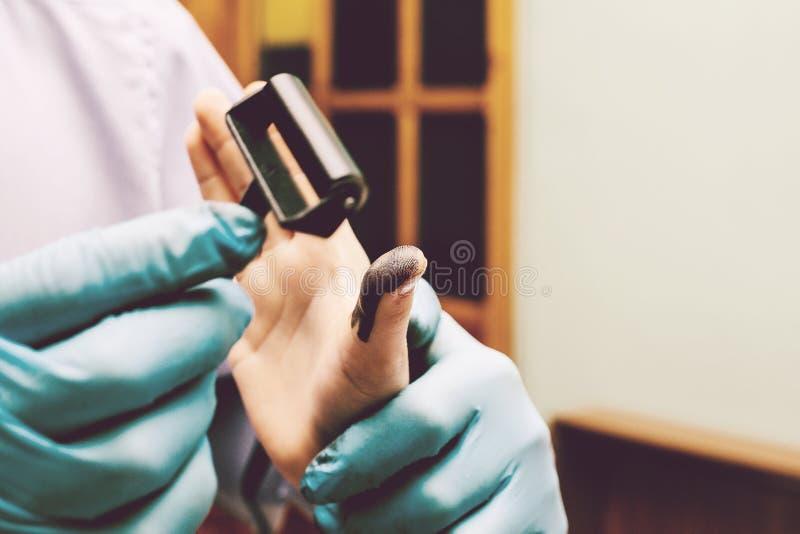 Utredaren tar fingeravtryck från misstänkten i brottet Utredning är ett brott brott royaltyfri fotografi