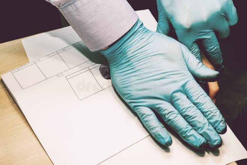 Utredaren tar fingeravtryck från misstänkten i brottet Utredning är ett brott brott arkivbilder