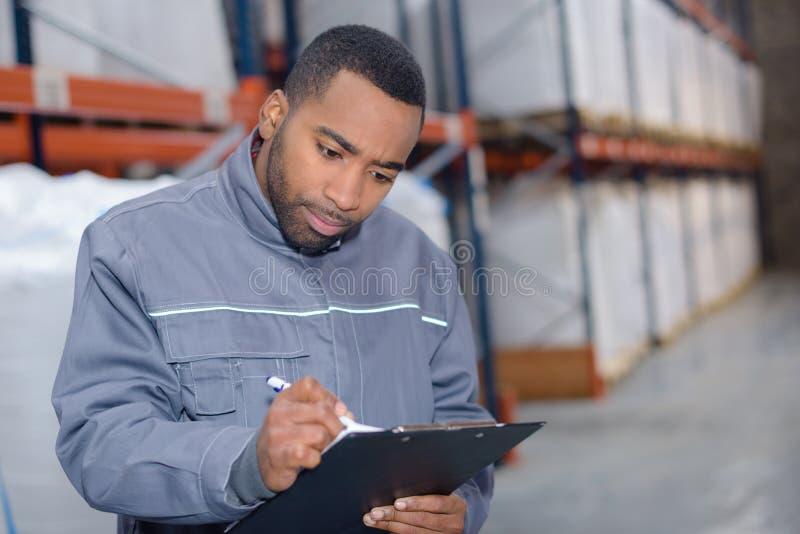 Utredning för lagerarbetarhandstil arkivfoto