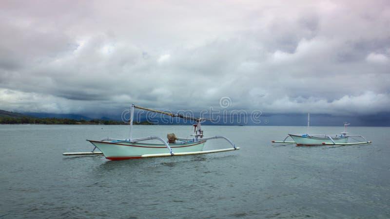 Utriggarefartyg på Lovina i Bali med stormiga moln arkivbild