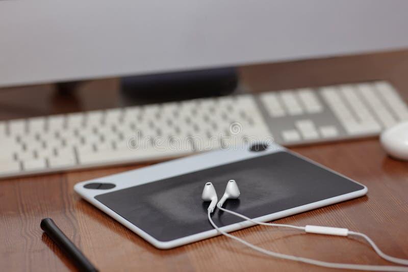 Utrustningen av fotografen eller grafic märkes- dator, mus, grafic minnestavla, nål och hörlurar Arbetsplats av konstpeop royaltyfri foto