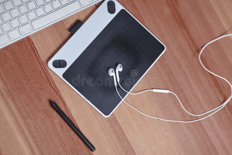 Utrustningen av fotografen eller grafic märkes- dator, mus, grafic minnestavla, nål och hörlurar Arbetsplats av konstpeop arkivfoto