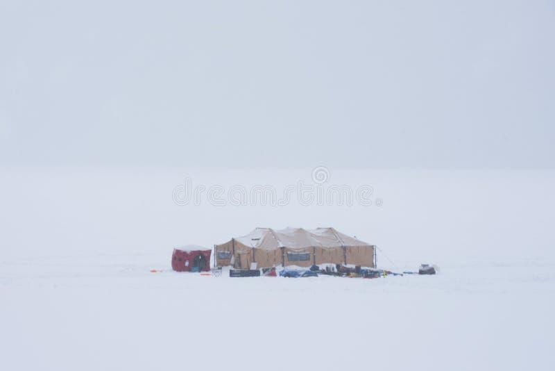 Utrustningtält på en djupfryst sjö arkivbilder