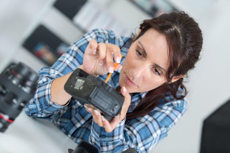 Utrzymanie fotografii kamera przy warsztatem obraz stock
