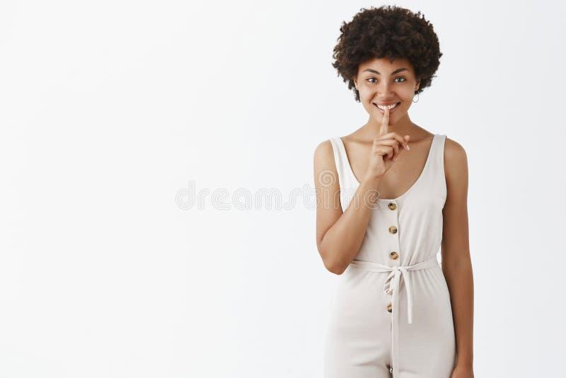 Utrzymujący sekrety bezpieczni Portret powabny młody amerykanin afrykańskiego pochodzenia uśmiecha się figlarnie mówić w białych  obrazy royalty free
