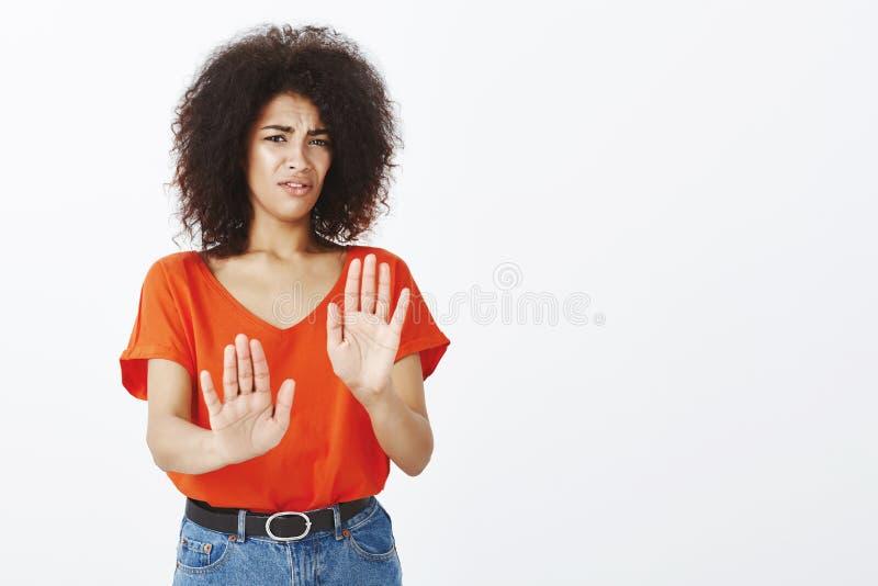 Utrzymuje mnie zdala od ja Zdegustowany intensywny atrakcyjny żeński uczeń z ciemną skórą i afro ostrzyżeniem ciągnie palmy w kie obrazy stock
