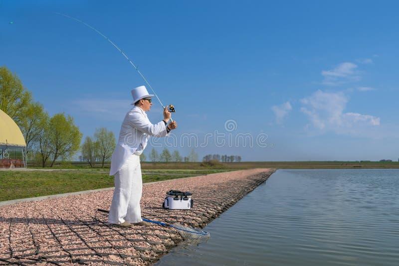 Utsökt fiske Fiskare i den vita dräktlåsfisken vid snurrstången på forellområdessjön arkivfoton