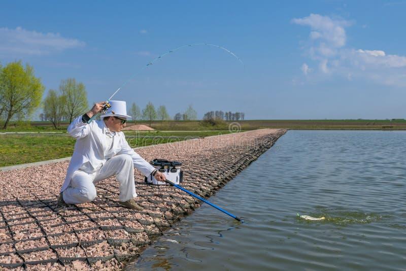 Utsökt fiske Fiskare i den vita dräktlåsfisken vid snurrstången på forellområdessjön royaltyfri fotografi