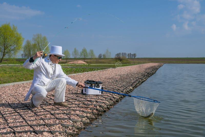 Utsökt fiske Fiskare i den vita dräktlåsfisken vid snurrstången på forellområdessjön royaltyfria foton