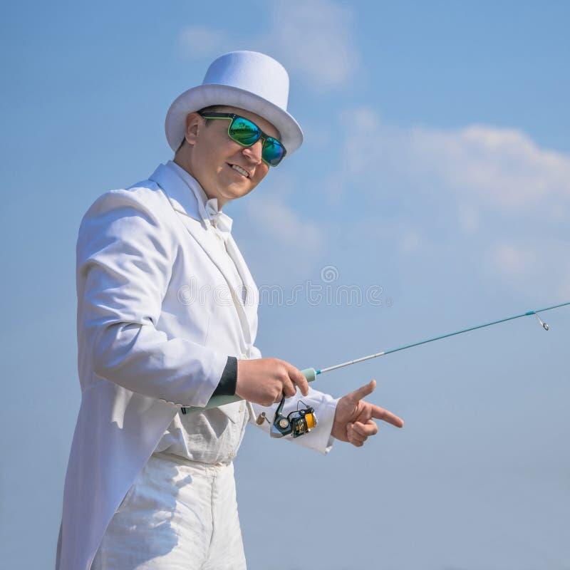 Utsökt fiske Fiskare i den vita dräktlåsfisken vid snurrstången på sjön arkivfoto