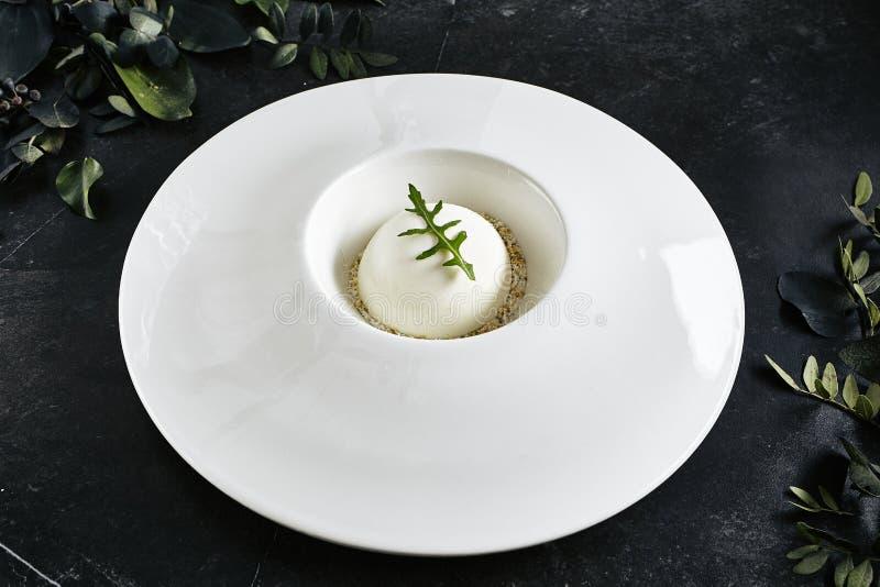 Utsökt tjänande som restaurangplatta av den vita parmesansfären med svarta Angus Tartare Top View royaltyfria foton