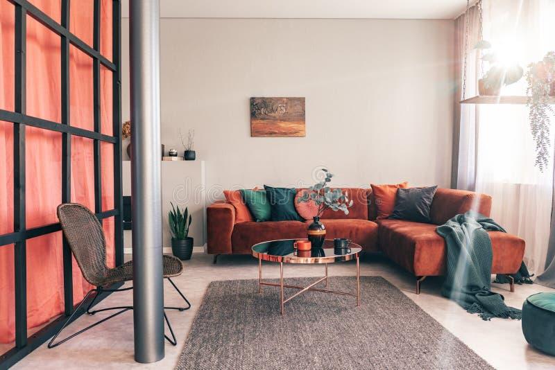 Utsökt vardagsruminre med den moderna möblemang och väggen med spröjs arkivfoto