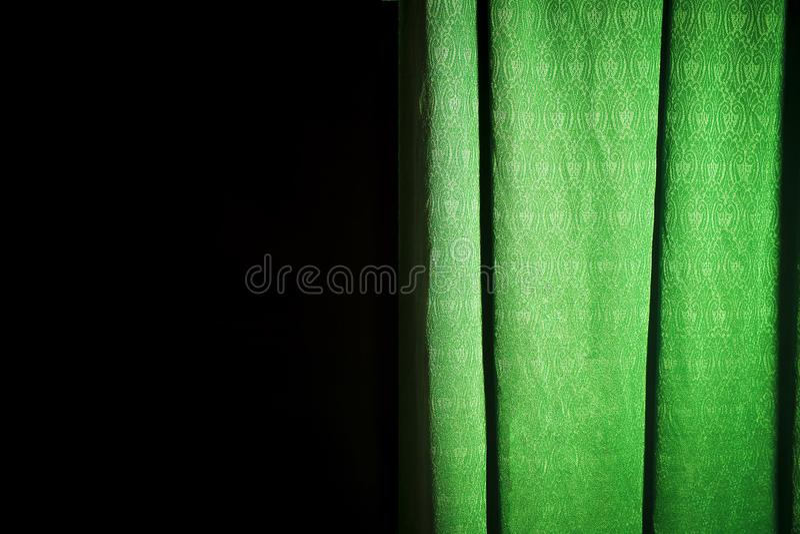 Utsatt grön gardin på en svart bakgrund arkivfoto