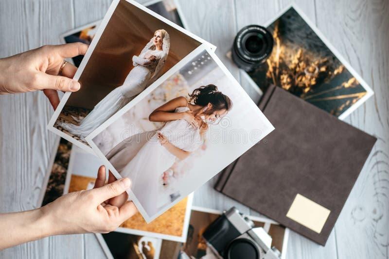 Utskrivavet gifta sig foto med bruden och brudgummen, en tappningsvartkamera, photoalbum och kvinnahänder med två foto royaltyfri fotografi