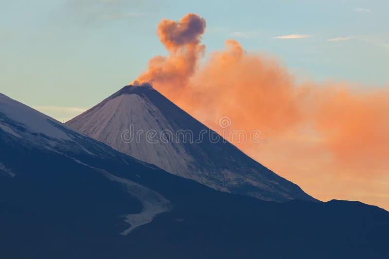 Utsläppaska från strålar för en vulkanKlyuchevskoy gryning av solen royaltyfri fotografi