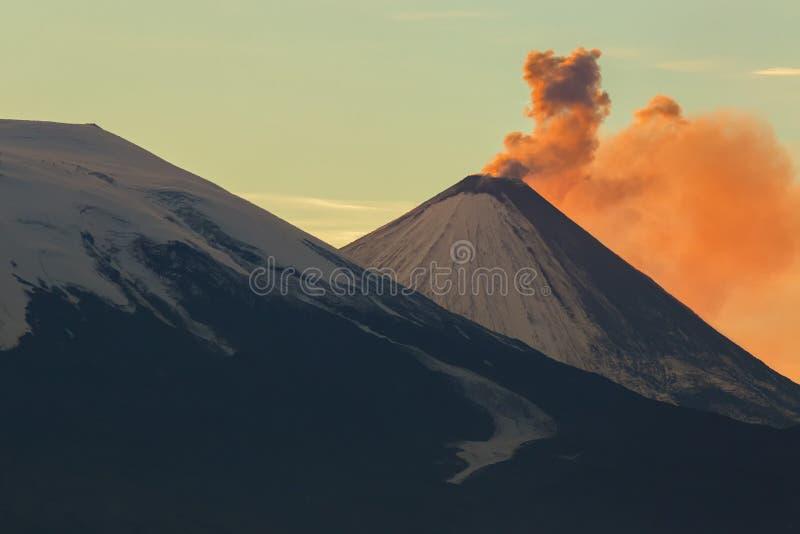 Utsläppaska från strålar för en vulkanKlyuchevskoy gryning av solen royaltyfri bild