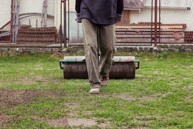Utsl?tn av gr?syttersida i tr?dg?rden ut Vuxen människa som använder gräsmattarullen för för att ge yttersida på samma nivå Somma arkivbilder