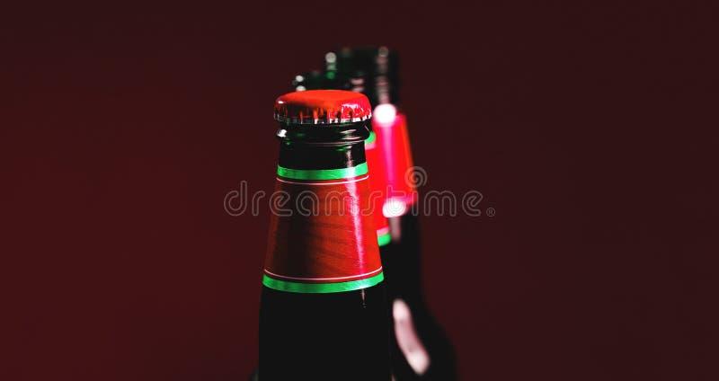 Utsmyckad brun flaska av läsken Ölflaskor med det röda locket och den färgrika texturerade etiketten fotografering för bildbyråer