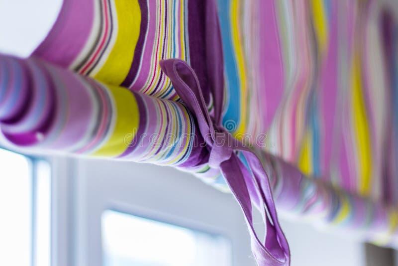 Utsmyckad färgglad gardin med linjer som täcker det hela fönstret royaltyfria foton