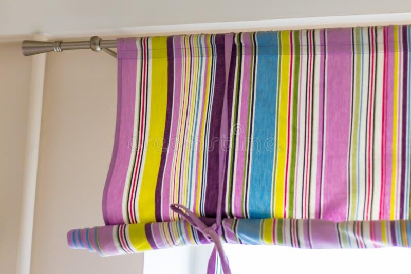 Utsmyckad färgglad gardin med linjer som täcker det hela fönstret arkivfoto