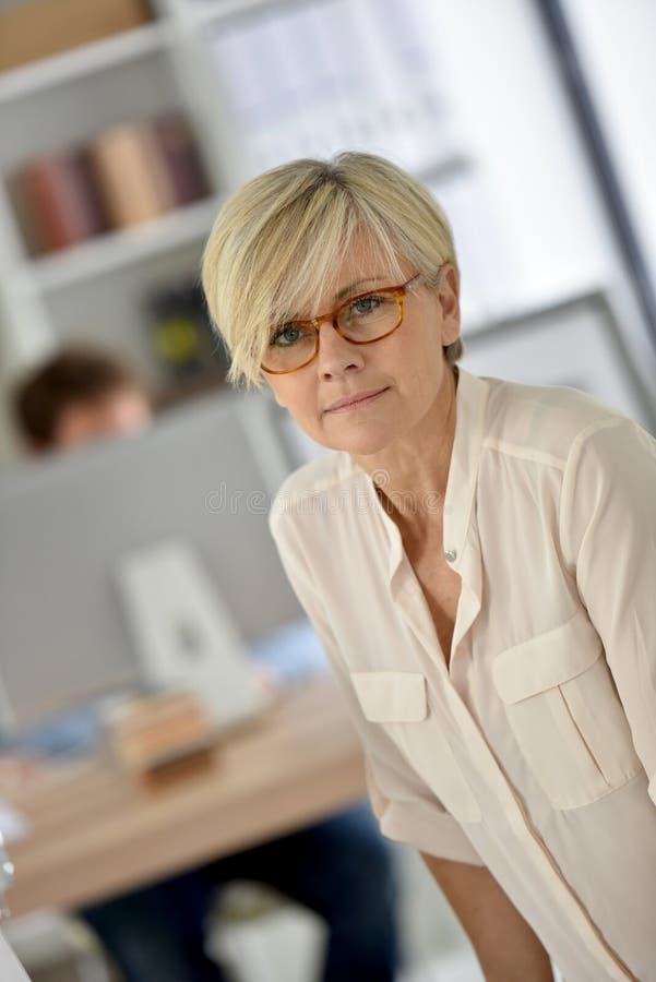 Utsmyckad hög affärskvinna på kontoret arkivbilder