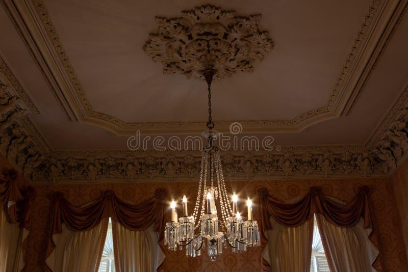 Utsmyckad kristallkrona i ett härligt rum med överdådiga gardiner och murbrukstöpningar, mjuka färger arkivbilder
