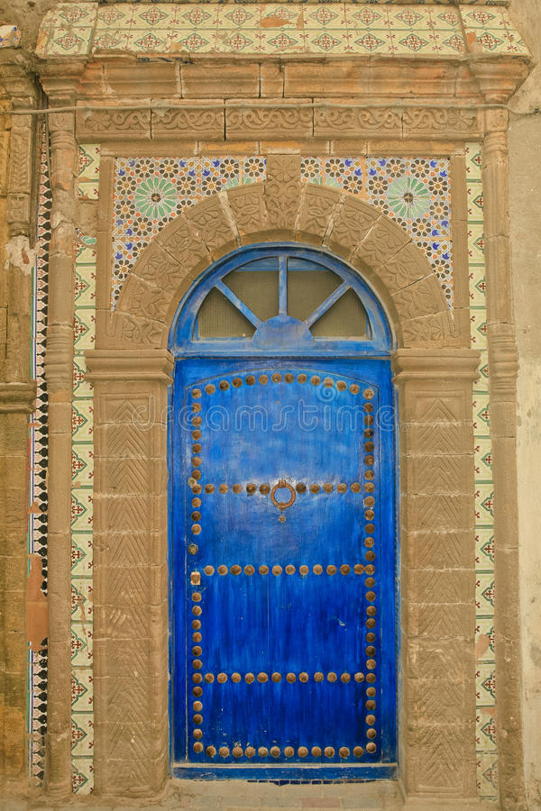 Utsmyckad marockansk blå dörr med tegelplattor arkivbilder