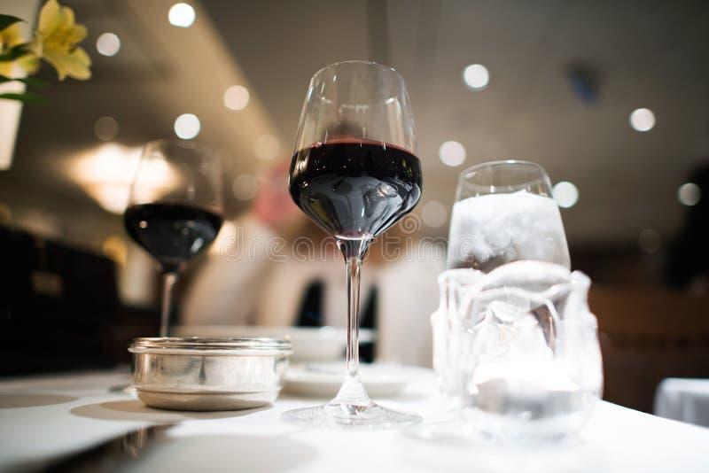 Utsmyckad matställe med rött vin fotografering för bildbyråer