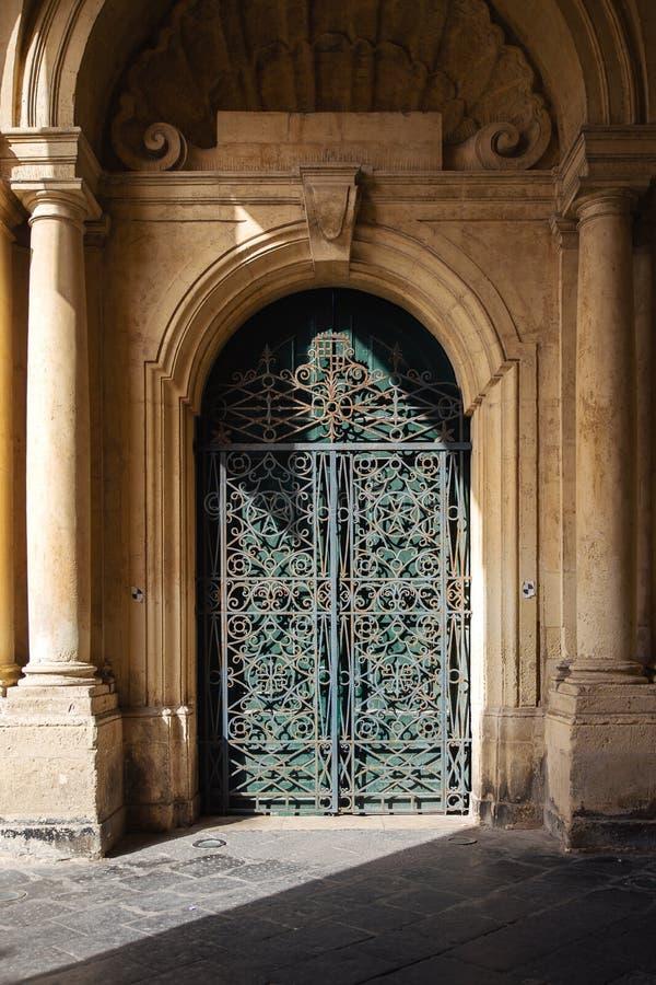 Utsmyckad metall- och trädörr till grandmaster'sens slottborggården i Valletta, Malta royaltyfria foton
