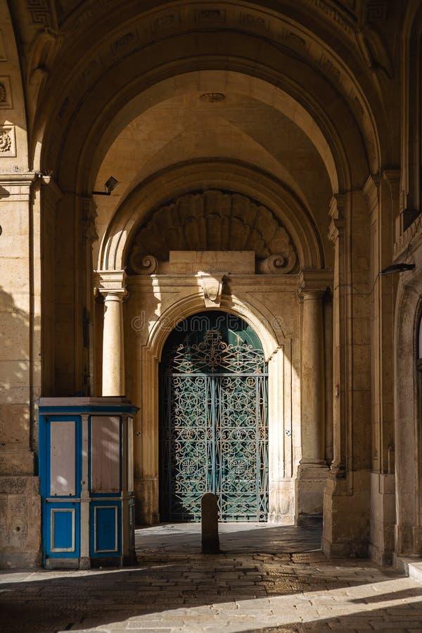 Utsmyckad metall- och trädörr till grandmaster'sens slottborggården i Valletta, Malta royaltyfria bilder